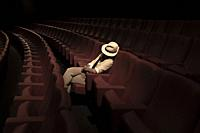 Woman with Hat Sleeping Alone in Movie Theater.