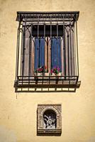 San Miguel de Allende, Barred window and religious sculpture on a facade in a colonial-era city, Bajío region, Central Mexico.