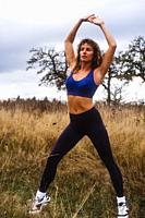 Woman outdoors doing exercise in sport bra and pants