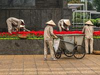 Gardeners working in the gardens in the Ho Chi Minh This style of hat is used primarily as protection from the sun and rain. When made of straw or mat...