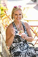 A pretty 59 year old blond woman having ice cream smiling at the camera at an outdoor cafe.