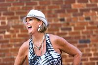 A pretty 59 year old blond woman laughing and looking away from the camera in front of a brick wall.