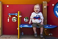 A happy 1 year old boy sits in a playground house in the suberb of El Carmel, Barcelona, Cataluna, Spain.