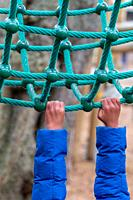 A young child hanging onto rope climbing equipment in Battersea Park, London.