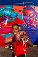 "5 year old Britton Grae-Chapman with boxing gloves in front of a huge mural painted of him by a local artist known as """"Detour"""" (actual name Thomas E..."