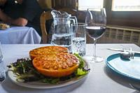 Big tomato cut in two halves with lettuce, salt and olive oil. Spain.