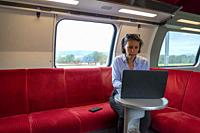 Business Woman Sitting on a Sofa and Working on Laptop in First Class in a Train in Switzerland.