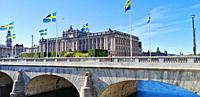 Swedish flags flying on Norrbro Bridge (North Bridge) in front of the Parliament House (Riksdagshuset), Stockholm, Sweden, Scandinavia