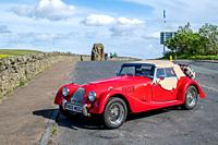 A red Morgan Roadster convertible rests parked on the side of the road near the Anglo-Scottish border at Carter Bar, Scotland.