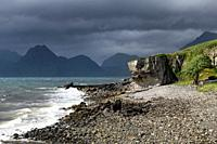 Rocky shore at Port na Cullaidh harbour Elgol with Red Cuillin Mountains under clouds at Loch Scavaig Isle of Skye Scotland UK.