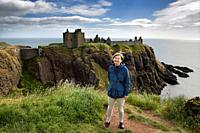 Scottish female tourist visitor at top of cliff above Old Hall Bay with Donnottar Castle ruins on the North Sea Scotland UK.