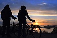 Couple with a bicycle on sunset in Kaivopuisto park, Helsinki, Finland.