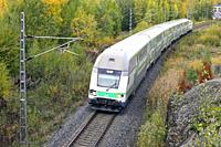 Salo, Finland - October 6, 2018: VR Group Passenger train at speed in autumn, elevated view from bridge.