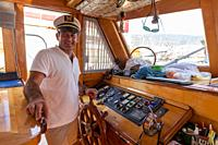 Captain at steering wheel on yacht/sailboat while boat is in harbour. Bodrum, Turkey.