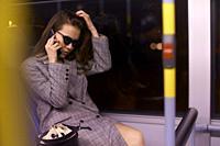 Woman in tram by night, talking by phone. Munich, Germany.