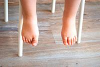Feet of a child sitting in a chair. Natural lighting.