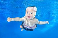Funny face portrait of little baby girl swimming and diving underwater with fun in pool on a blue water background. Healthy family lifestyle and child...