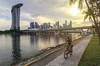 Singapore, Singapore - October 17, 2018: Woman cycling in down town in front of the Marina Bay Sands and Modern Art Museum at sunset.