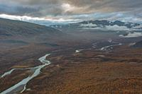 View over Rapa valley from Mount Namatj in September, bich trees are orange and water in the river are turqoise, Sarek national park, Swedish Lapland,...