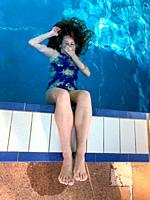 Girl playing holding her breath under water at the edge of a swimming pool.