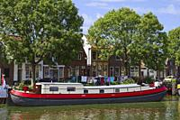 House boat in Enkhuizen, small city of northern Holland, boat transformed into home, behind traditional houses.