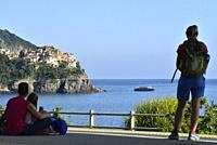 Italy, Liguria, Cinque Terre National Park, World Heritage Site, Corniglia station, Hikers waiting for the next train and looking at Manarola.