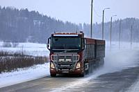 Salo, Finland - December 22, 2018: Red Volvo FH16 transporter driving on snowy highway in winter snowfall in South of Finland.