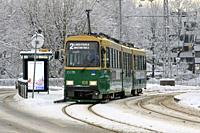 Helsinki, Finland - January 9, 2019: Green HSL tram No. 2 on a tram stop on a day of winter with snowfall in Helsinki.