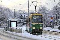 Helsinki, Finland - January 9, 2019: Green HSL tram No. 2 on a tram stop on a day of winter with light snowfall in Helsinki.