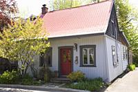 Old 1862 white with red and grey trim cottage style home facade in spring, Quebec, Canada.