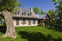 Old circa 1740 Canadiana fieldstone cottage style home facade with new extension in spring, Quebec, Canada.