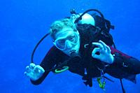 Close up of femal diver showing the ok sign.