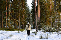 A man is walking through a snowy winter forest