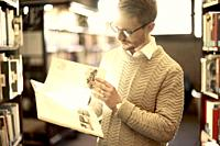 man browsing book, library, glasses, student, university, knowledge.