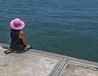 Woman sits calmly on a pier watching the sea. Port Douglas, Australia.