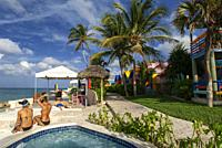 Tourists at swimming pool and spa of Hotel Compass Point Resort at Love beach Nassau, Bahamas, Caribbean. Brightly Colored Cottages At Compass Point B...