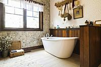 Antique style freestanding roll top bathtub in ceramic tile floor En suite on upstairs floor inside a LEED certified Country home