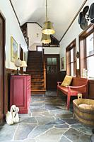 Flagstone hallway with antique wooden red-wine dresser and sitting bench inside a New Hampton style home