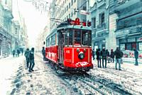 Winter view of nostalgic red Tram and people in daily life while snowing at popular Istiklal Street of Beyoglu,Istanbul,Turkey. 07 January 2017.