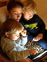 Woman read a tablet computer with two boys, 3 years old, in Scania, Sweden.