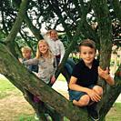 Four children climbing a tree in Ystad, Scania, Sweden.