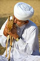 India, Rajasthan, Jodhpur region, Bishnoi devotee hugging a wild baby Chinkara (Indian gazelle). . .