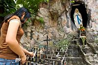 A woman places candles to the Virgin in the Cathedral of Tagbilaran. Tagbilaran. Bohol. Cathedral of San Jose the worker, known as the Cathedral of Ta...