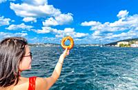 Beautiful Chinese woman holds traditional Turkish simit (bagel) with view of Bosphorus in Istanbul,Turkey.