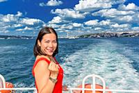 Beautiful Chinese woman cruises in ferry with view of Istanbul Bosphorus in Turkey.