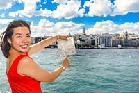 Beautiful Chinese woman shows Galata Tower on map while cruising in Istanbul,Turkey.