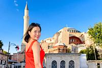 Beautiful woman poses with view of Hagia Sophia on background in Istanbul,Turkey.
