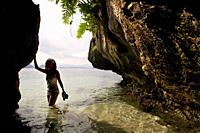 A tourist in Cudugman cave. Bacuit archipelago. Palawan. El Nido. Philippines. There are still some pirate bones that haunted the area.