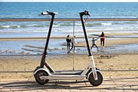 Electric scooters and people in background. Beach of Castellon. Valencian Community. Spain.