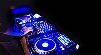 Soft view of man hand disc jockey mixing and blending music tracks on his deck in the darkness of a party or night club. Copy space for text.